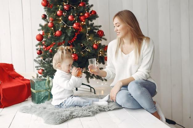Женщина весело готовится к рождеству. мать в белом свитере, играя с дочерью. семья отдыхает в праздничном зале. Бесплатные Фотографии