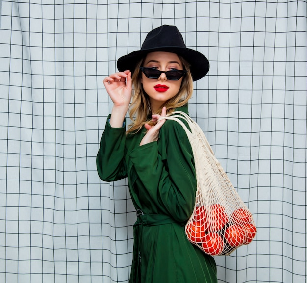 Woman in hat and green cloak in 90s style with net bag Premium Photo