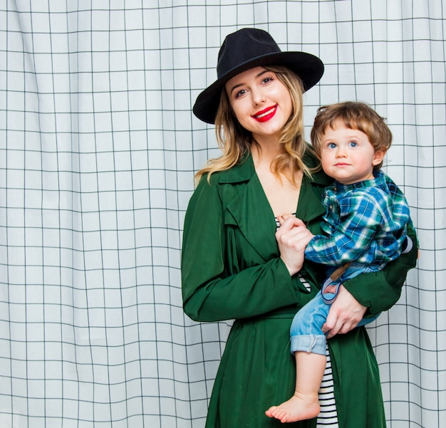 Woman in hat and green cloak in 90s style with toddler boy Premium Photo