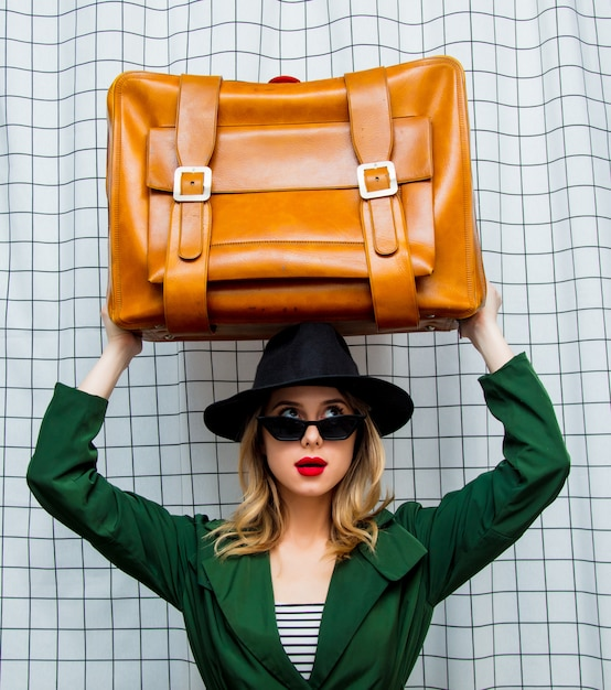 Woman in hat and green cloak in 90s style with travel suitcase Premium Photo