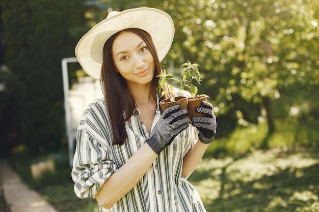 La donna in un cappello che tiene i vasi da fiori Foto Gratuite