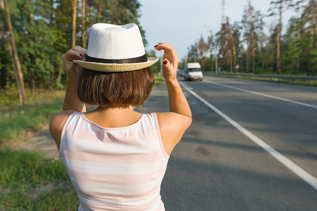 Woman in hat, looking forward to the road, copy space Premium Photo