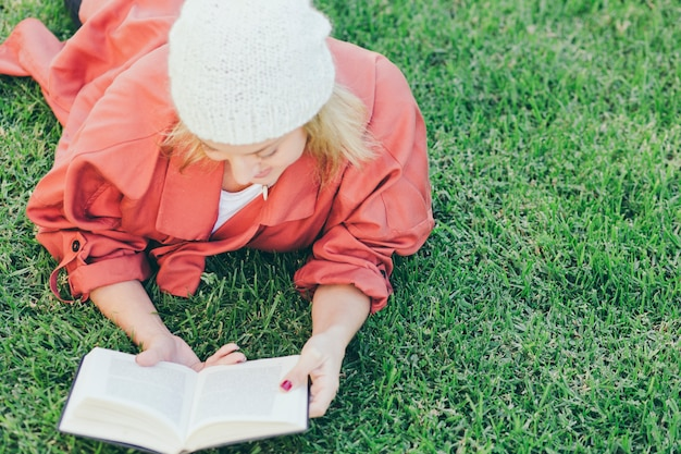 Woman in hat reading book on grass Free Photo
