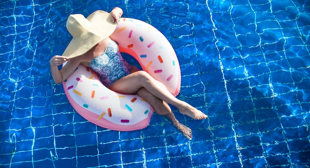 A woman in a hat relaxes on an inflatable circle in the pool. Free Photo