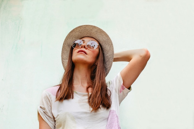 Woman in hat and sunglasses looking up Premium Photo