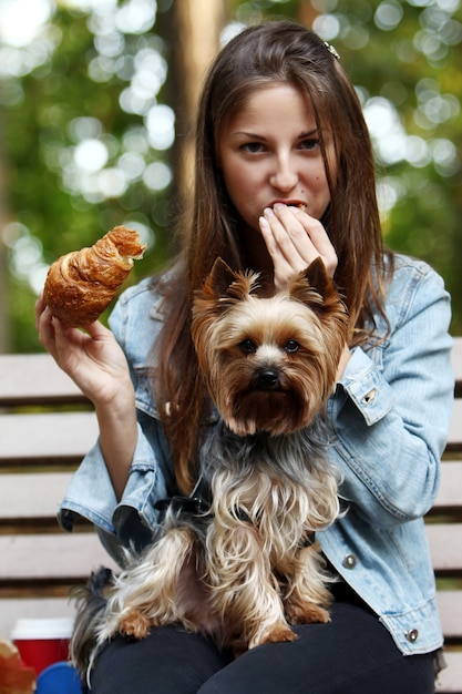 Woman have lunch while strolling with her dog Free Photo