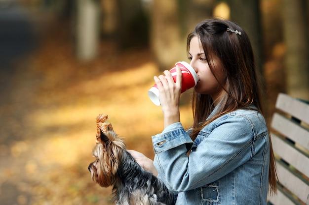女性は彼女の犬と散歩しながら昼食をとる 無料写真