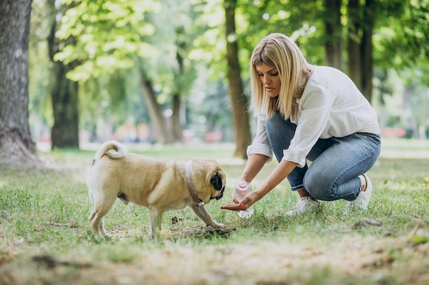 パグ犬ペットと公園で散歩を持つ女性 無料写真