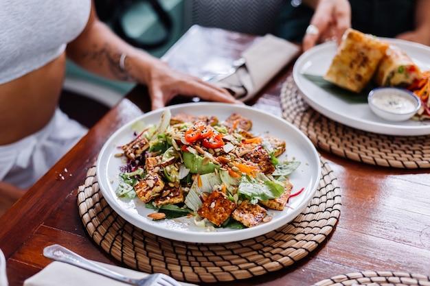 Donna che mangia insalata di pasto vegetariano vegano sano colorato nella luce del giorno naturale del caffè estivo Foto Gratuite