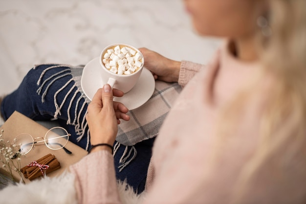 Woman having cup of hot cocoa with marshmallows while reading Free Photo