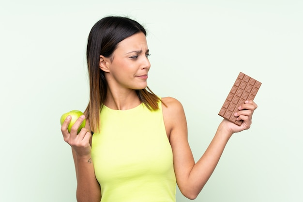 Woman having doubts while taking a chocolate tablet in one hand and an apple in the other Premium Photo