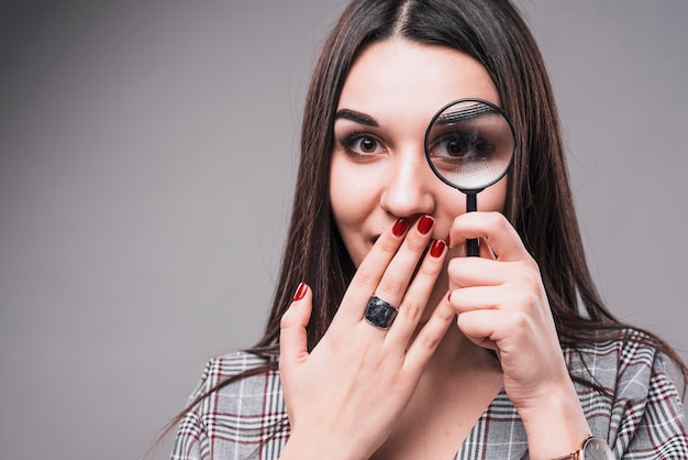 Woman having fun with magnifying glass Free Photo