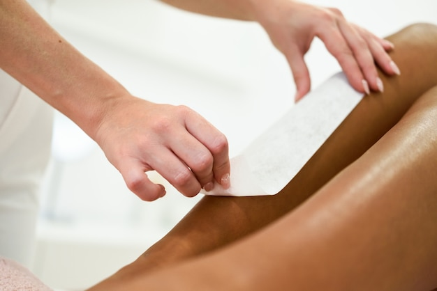 Woman having hair removal procedure on leg applying wax strip Free Photo