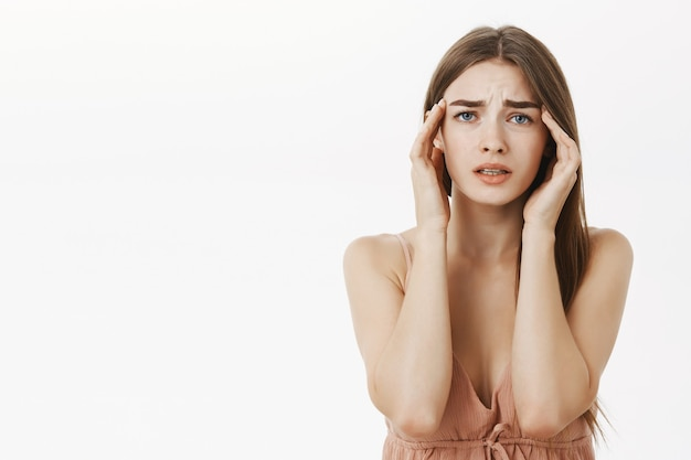 Женщина, страдающая головной болью во время менструации, чувство разочарования и беспокойства, прикосновение к вискам, хмурясь от дискомфорта, страдает от болезненного ощущения или мигрени, встревожено. Бесплатные Фотографии
