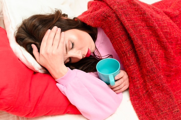 Woman having a headache while staying in bed Free Photo