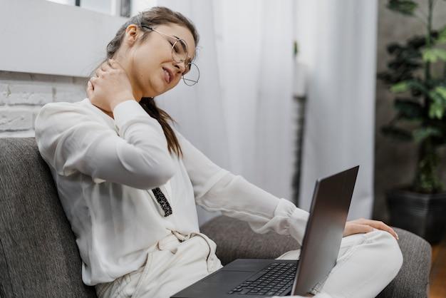 Donna che ha un mal di collo mentre lavora a casa Foto Gratuite