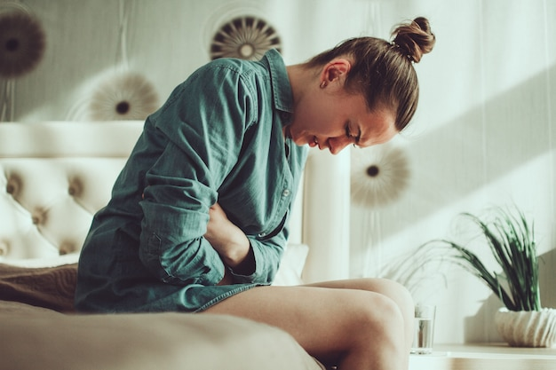 Woman having painful stomach ache. female suffering from abdominal pain. pain in the abdomen due to menstruation period and pms. inflammation in the body and infection, cystitis Premium Photo