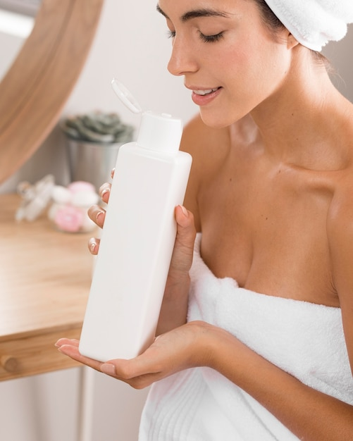 Woman having a relaxing day and smelling a body lotion Free Photo