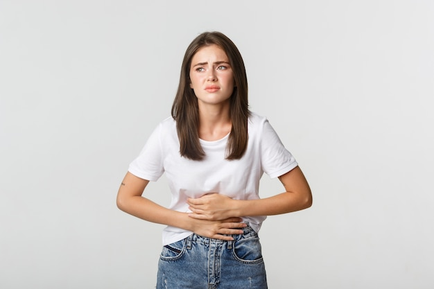 Woman having stomach ache, bending and holding hands on belly