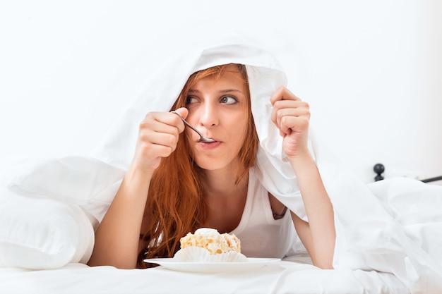 Woman having sweet cake  at bed Free Photo