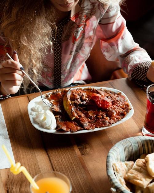 Woman having turkish iskender doner with tomato sauce and yogurt. Free Photo