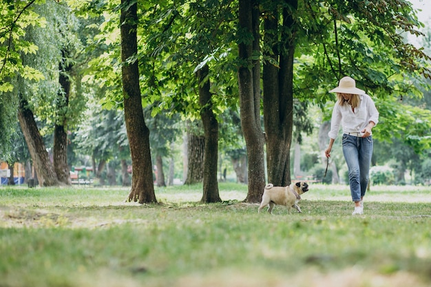 Woman having a walk in park with her pug-dog pet Free Photo