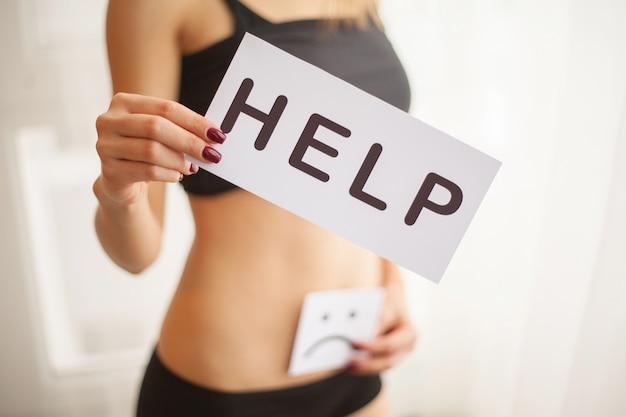 Woman health. female body holding symbol help card near stomach Premium Photo