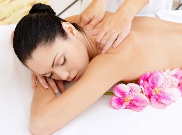 Donna sul sano massaggio del corpo nel salone della stazione termale. concetto di trattamento di bellezza. Foto Gratuite