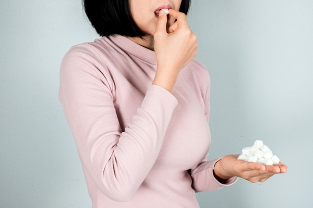 The woman held a sugar cube and was feeling ill with sugar cubes. Premium Photo