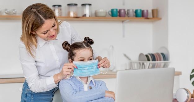 Donna che aiuta sua figlia a mettere una maschera medica Foto Gratuite