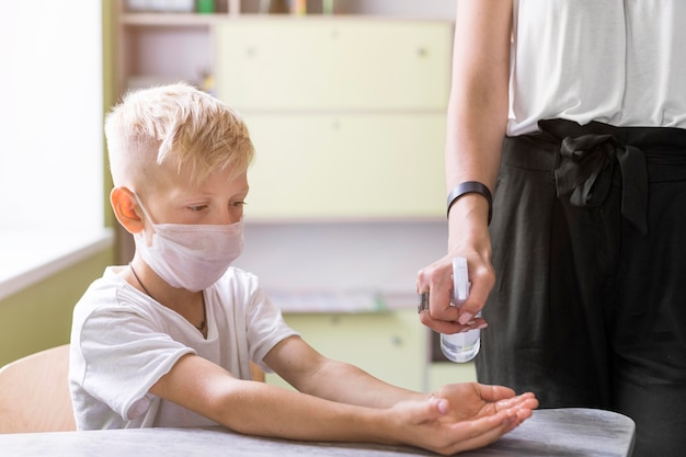 Woman helping a student disinfecting his hands Premium Photo
