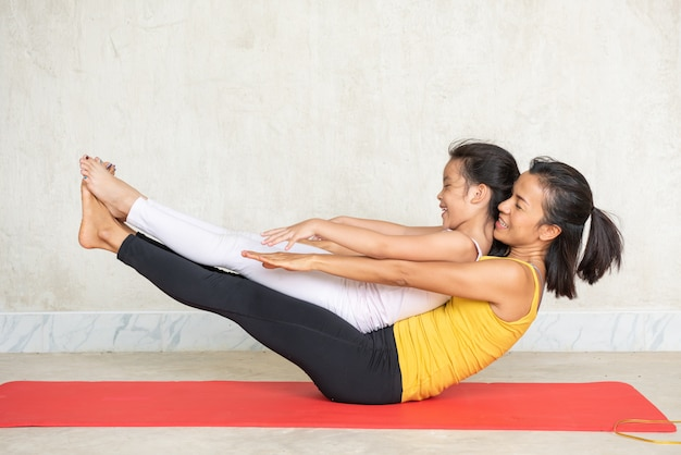 Woman and her charming little daughter doing yoga Free Photo