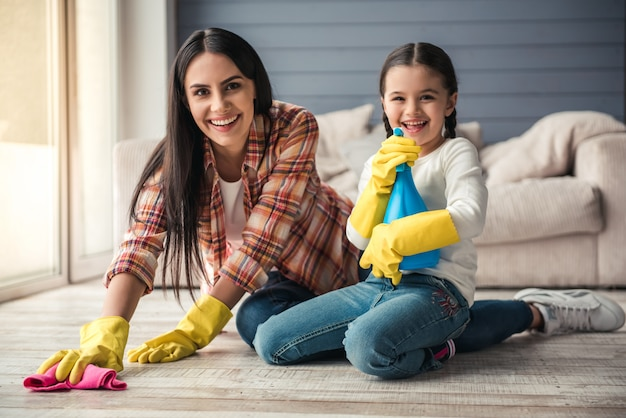 Woman and her daughter are smiling while cleaning floor. Premium Photo