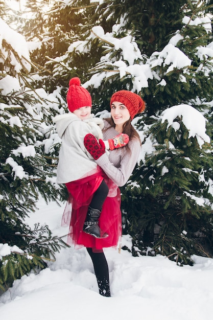 Woman and her daughter have fun in the winter forest Premium Photo