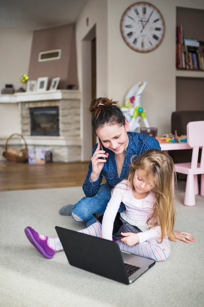 Woman and her daughter sitting on carpet with electronic gadgets Free Photo