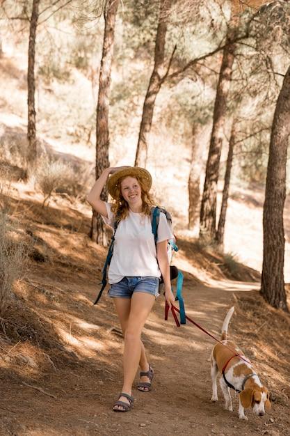 La donna e il suo cane che camminano nei boschi alla luce del giorno Foto Gratuite
