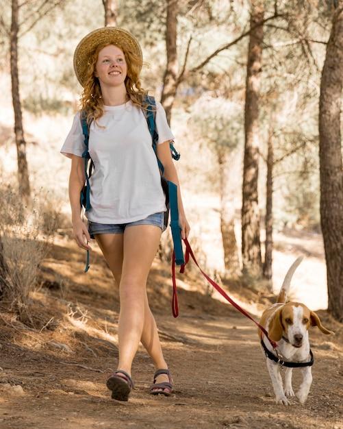 La donna e il suo cane che camminano nel bosco Foto Gratuite
