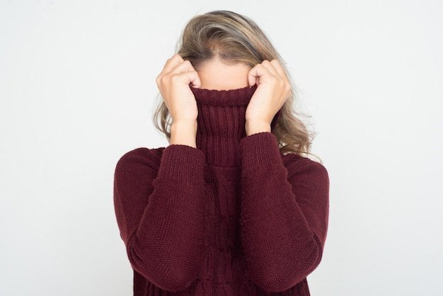 Woman hiding face in turtleneck Free Photo