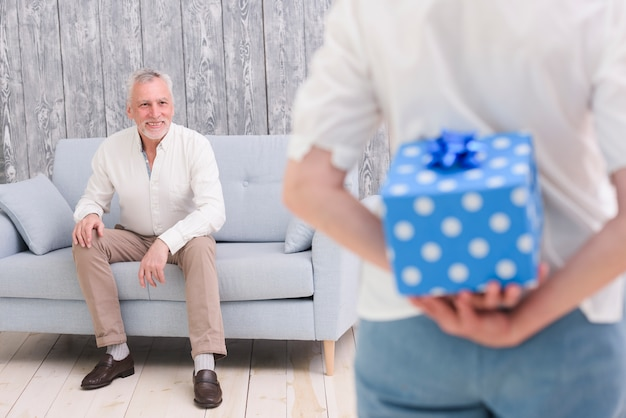Woman hiding gift box behind her back in front of her happy husband sitting on sofa Free Photo