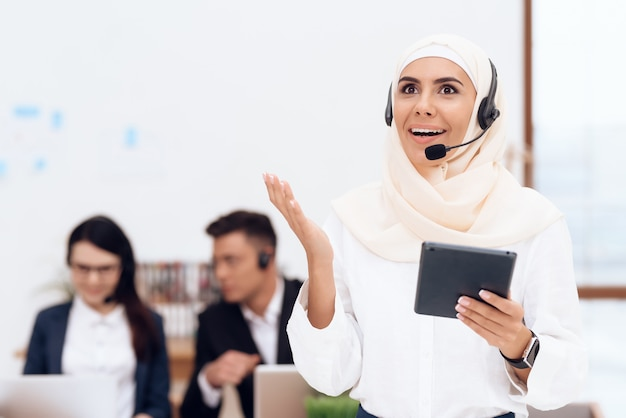 The woman in the hijab stands in the call center Premium Photo