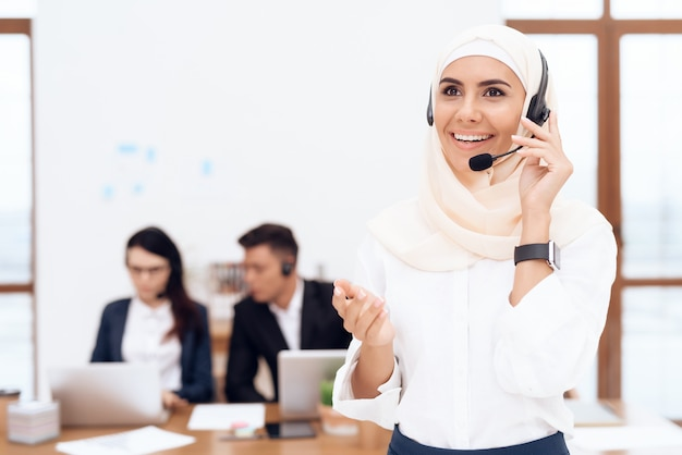 The woman in the hijab stands in the call center. Premium Photo