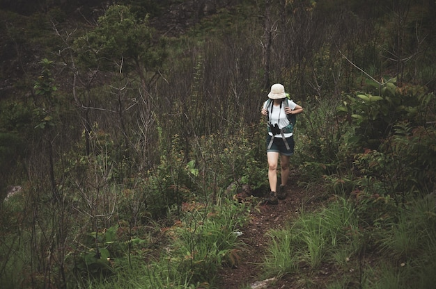 Woman hiking at sunset mountains with heavy backpack travel lifestyle wanderlust adventure concept summer vacations outdoor alone into the wild Premium Photo