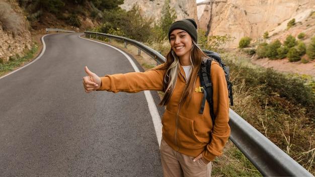 Donna autostop per un'auto Foto Gratuite