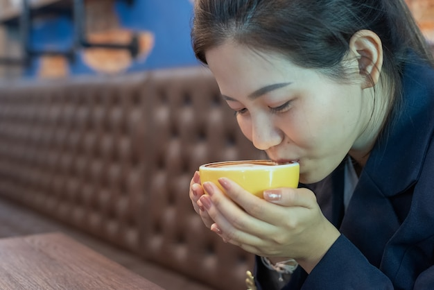 Woman hold coffee cup and drink in coffee shop Premium Photo