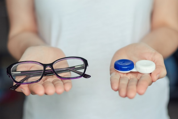 Woman hold contact lenses and glasses in hands. concept of choice of vision protection Premium Photo