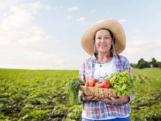 野菜がいっぱい入ったかごを持った女性 Premium写真