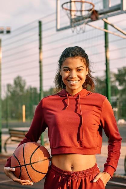 Женщина, держащая баскетбол на открытом воздухе Бесплатные Фотографии