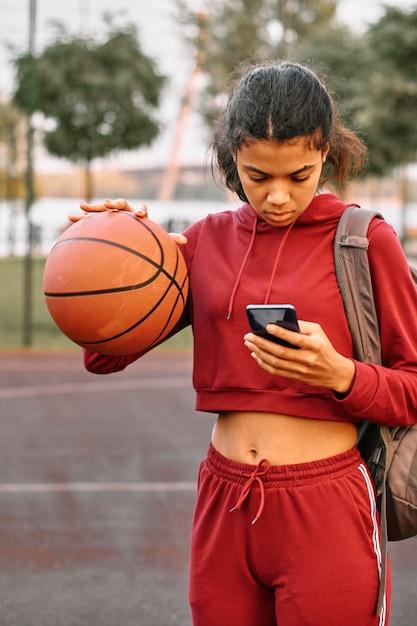 Женщина, держащая баскетбол, проверяя свой телефон Бесплатные Фотографии