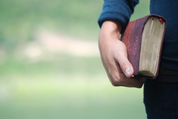 Женщина, держащая библейскую книгу. Premium Фотографии