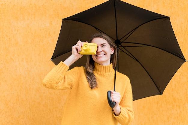 Женщина держит черный зонт и желтый фотоаппарат Бесплатные Фотографии